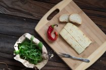 Elevated view of cheese, chili, arugula and bread over wooden table — Stock Photo