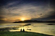 Силует Індонезії острові Ломбок, двох жінок, сидячи на захід сонця над морем — стокове фото