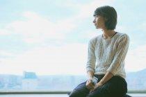 Retrato de uma jovem mulher olhando pela janela — Fotografia de Stock