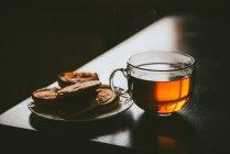 Chá de gentrice e panquecas em fundo escuro — Fotografia de Stock