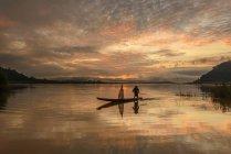 Homme debout dans le bateau de pêche au coucher du soleil, Mékong, Thaïlande — Photo de stock
