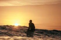 Silhouette de Surfer sur la planche de surf au coucher du soleil, en Californie, Amérique, Etats-Unis — Photo de stock