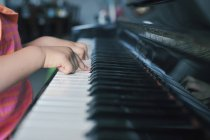 Close-up hands of little girl playing piano — Stock Photo