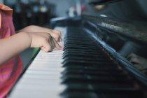 Nahaufnahme der Hände eines kleinen Mädchens beim Klavierspielen — Stockfoto
