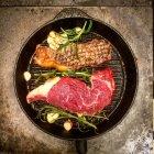 На гриле стейки с розмарином и чесноком в сковороде — стоковое фото