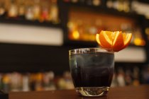 Black cocktail with star shaped orange on bar counter — Stock Photo