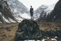 Vue arrière de la femme debout sur un rocher entre les montagnes, Ossétie du Nord, Russie — Photo de stock
