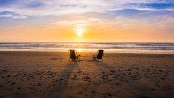 Malerischer Blick auf zwei Stühle am Strand bei Sonnenuntergang, Kalifornien, Amerika, USA — Stockfoto