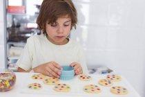 Concentré garçon faire des cookies dans la cuisine — Photo de stock