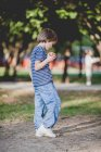 Boy standing in park and eating apple — Stock Photo