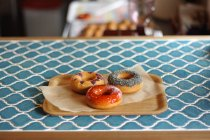 Three tasty donuts on baking paper on wooden tray — Stock Photo