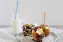 Ricoperto di cioccolato e caramello mele sui bastoni con una bottiglia di latte — Foto stock