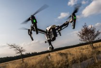 Drone camera flying mid air against beautiful field landscape — Stock Photo