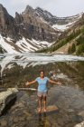 African american girl standing with outstretched arms, Lake Agnes, Banff National Park, Alberta, Canada — Stock Photo