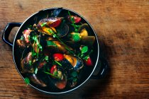 Saucepan with mussels, tomatoes and herbs, top view — Stock Photo