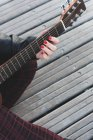 Cropped image of girl with red nails playing the guitar — Stock Photo