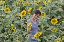 Sorridente Adolescente ragazza guardando girasoli in campo — Foto stock