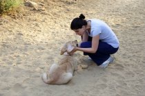 Femme jouant avec chien chiot golden retriever dans le sable — Photo de stock