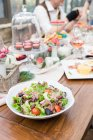 Плита салату на стіл з кекси, люди на розмитість фону — стокове фото