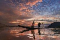 Силует людини кидаючи рибальську мережу, річки Меконг, Sangkhom, Таїланд — стокове фото
