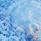 Legs of Boy splashing in swimming pool — Stock Photo