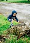 Мальчик в куртке в капюшоне забирается на бревно — стоковое фото