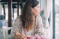 Mulher desfrutando de uma xícara de café no café e olhando através da janela — Fotografia de Stock