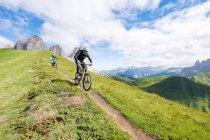 Man and woman mountain biking along trail, Dolomites, Italy — Stock Photo