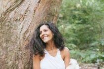 Портрет улыбающейся женщины, прислонившейся к дереву в парке — стоковое фото