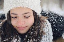 Retrato de uma menina vestindo roupas quentes sorrindo na neve — Fotografia de Stock