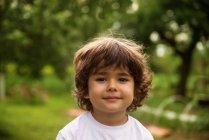 Portrait of smiling boy in summer garden — Stock Photo