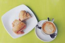 Taza de café y rollo de jamón sabroso, vista superior - foto de stock