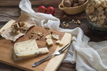 Cheese with croutons and walnuts over wooden table — Stock Photo