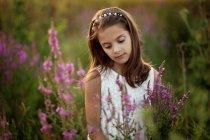Portrait of girl standing in meadow between flowers — Stock Photo