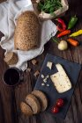 Cheese, bread, red wine and chili peppers over wooden table, top view — Stock Photo