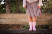 Faible section de Girl wearing caoutchouc rose bottes holding Couronne — Photo de stock