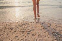 Cropped image of female legs walking on beach — Stock Photo