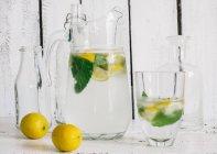 Стеклянный кувшин со свежим лимоном, лаймом, мятой и кубиками льда — стоковое фото