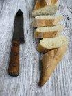 Скибочки хліба, ножем на дерев'яним столом, підвищені подання — стокове фото
