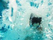 Подводный вид мальчика, прыжки в бассейн — стоковое фото