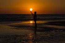Silhouette of boy standing on beach balancing sun on finger — Stock Photo