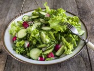 Чаша з огірки, редис і салат салат над дерев'яний стіл — стокове фото
