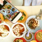 Donna fotografare il cibo con il telefono mobile — Foto stock