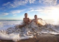 Two caucasian boys having fun in ocean water — Stock Photo