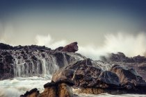 Waves crashing on rocks on beach, Karang Beureum, Sawarna, Indonesia — Stock Photo