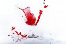 Glass of red liquid in broken wine glass — Stock Photo