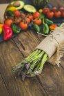 Букет з свіжих спаржа загорнуті в лляну тканину з фруктів і овочів на дерев'яні таблиці — стокове фото