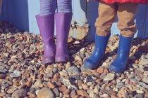 Image recadrée de deux enfants dans wellies à la plage — Photo de stock