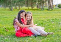 Two little caucasian girls hugging on grass at park — Stock Photo