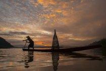 Силует людини рибалка в озеро на заході сонця, Таїланд — стокове фото